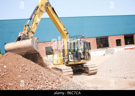 Excavator moving material on construction site - Stock Photo