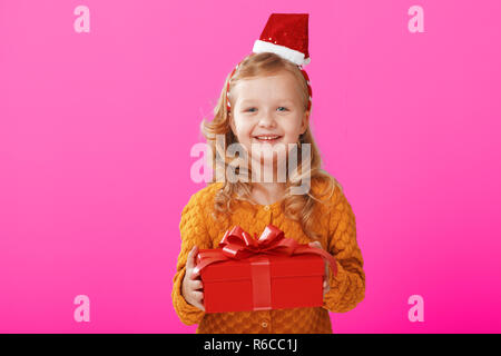 Happy little child girl in a warm knitted sweater and cap Santa Claus is holding a red box with a gift on a pink background. The concept of celebratio - Stock Photo