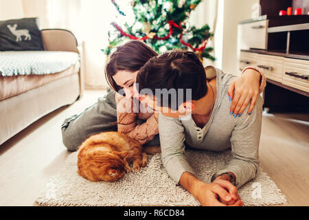 Couple in love lying by Christmas tree and playing with cat at home. Man and woman relaxing - Stock Photo