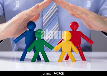 Human Hand Protecting Human Figures - Stock Photo