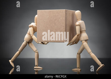 Wooden Dummy Couple Carrying Cardboard Box - Stock Photo