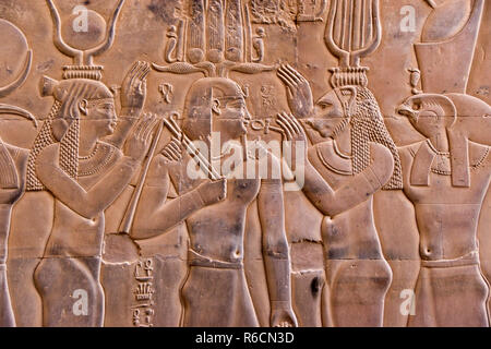 A bas relief image of Egyptian gods and pharaohs carved on a wall at the Temple of Kom Ombo, Egypt. - Stock Photo