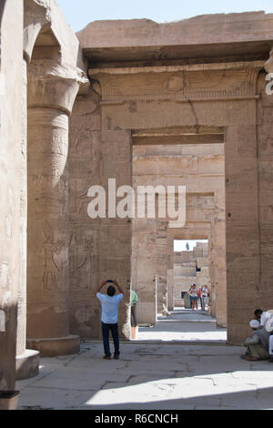 A tourist makes photos at the Temple of Kom Ombo, an unusual double temple in Kom Ombo, Aswan Governorate, Egypt. - Stock Photo