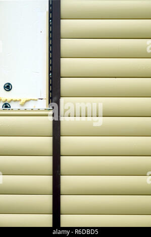 Siding panels mounting over insulation on building wall front view closeup - Stock Photo