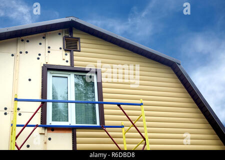 Beige siding panels mounting with scaffolding on beautiful rural house in sunny day over blue sky front view - Stock Photo