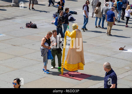 Street performer dressed as Yoda. The performer is creating the illusion that he is floating. London, United Kingdom - Stock Photo