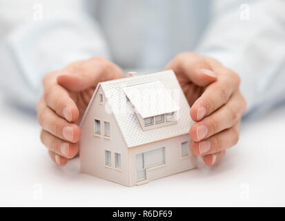 Property insurance. House miniature covered by hands. - Stock Photo