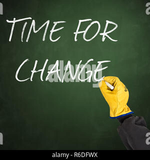worker hand with protective glove writing words time for change on green chalkboard - Stock Photo