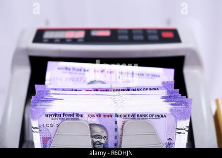 Indian banknote in the money counting machine. Isolated on the white background. - Stock Photo