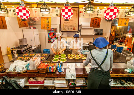 Cook Chef Preparing Okonomiyaki On Hot Plates In Gion, Kyoto, Japan - Stock Photo