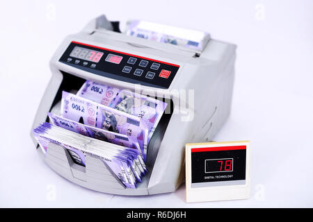 Indian banknotes at the currency counter machine. Isolated on the white background. - Stock Photo