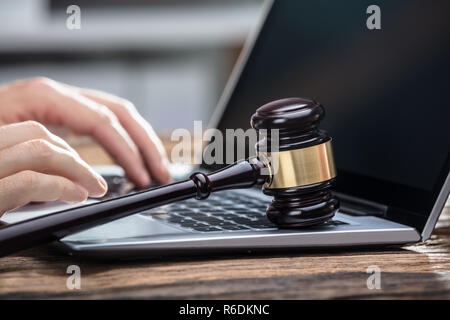 Businessperson's Hand Using Laptop On Wooden Desk - Stock Photo