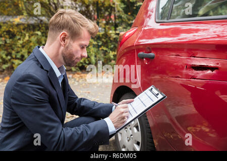 Insurance Agent Examining Car After Accident - Stock Photo
