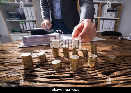 Businessperson Calculating Stacked Coins - Stock Photo