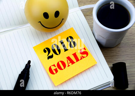 Writing text showing 2018 Goals. Business concept for financial planning, business strategy written sticky note empty paper, Wooden background with copy space, Coffee and marker - Stock Photo