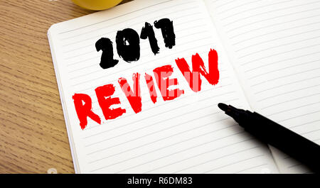 Handwritten text caption showing 2017 Review. Business concept writing for Annual Summary Report written on notebook with copy space on book background with marker pen - Stock Photo