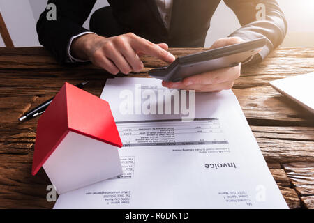 Businessperson Using Calculator For Calculating Invoice - Stock Photo
