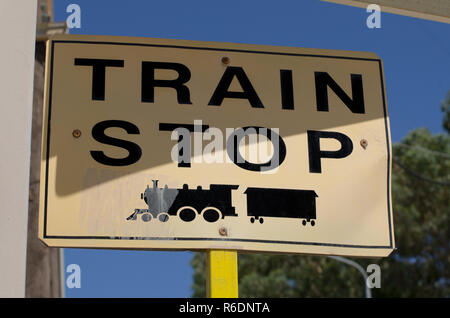 Road sign with the inscription in English 'train stop' and the symbol of the locomotive black - Stock Photo