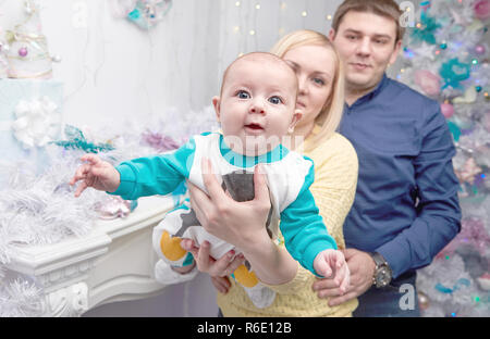 loving parents show their baby Christmas gifts - Stock Photo