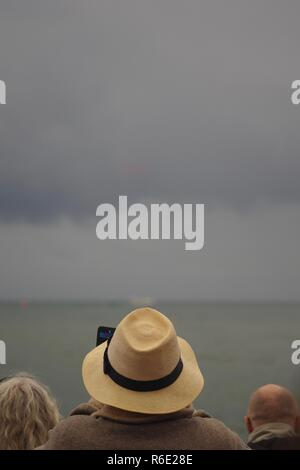 Spectators Watching The Red Arrows, Royal Air Force Aerobatic Team. Displaying at Sidmouth Regatta 2018, against a Moody Grey Sky. East Devon, UK. - Stock Photo