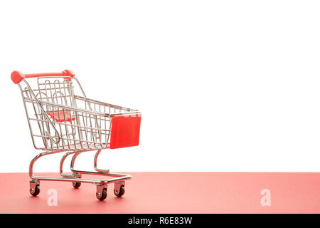 Small empty shopping cart with red handle. On red and white background with copy space - Stock Photo
