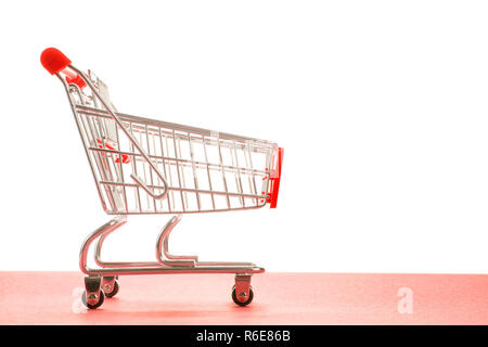 Small empty shopping cart with red handle side view. On red and white background with copy space - Stock Photo
