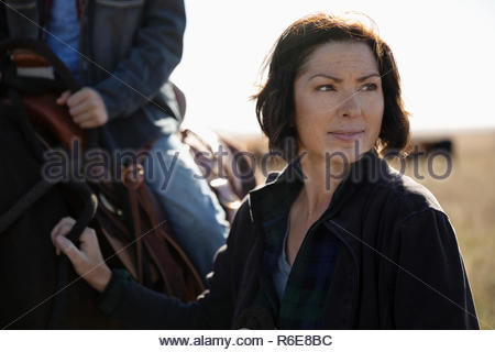 Woman standing next to horse - Stock Photo