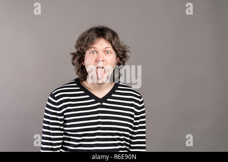 Portrait of funny shaggy crazy handsome man in striped sweater looking at camera with big open mouth and tongue out, teases. Wide opened eyes indoor studio shot, isolated on gray background. - Stock Photo