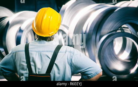 worker in protective uniform and protective helmet in front of sheet tin metal rolls in production hall - toned image, retro film filtered in instagra - Stock Photo