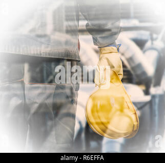Double exposure of worker with protective helmet in front of production oil plant - Stock Photo