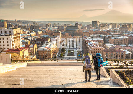Yerevan, Armenia - Jan 8th 2018 - A couple of backpackers enjoying the sunset at the top of the Cascade with Yerevan city and a mountain in the backgr - Stock Photo