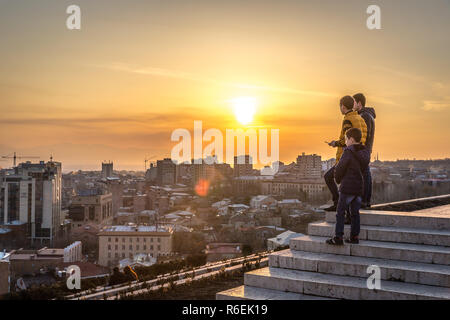 Yerevan, Armenia - Jan 8th 2018 - Locals enjoying the sunset at the top of the Cascade with Yerevan city in the background - Stock Photo
