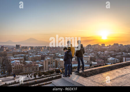 Yerevan, Armenia - Jan 8th 2018 - Locals watching the sunset at the top of the Cascade with Yerevan city in the background - Stock Photo