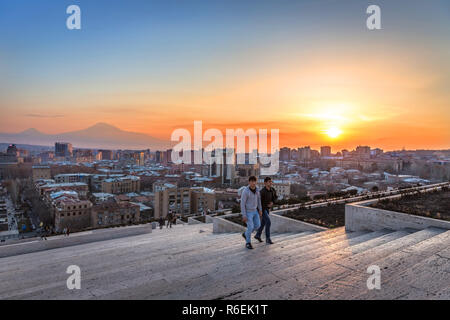 Yerevan, Armenia - Jan 8th 2018 - Locals at the sunset at the top of the Cascade with Yerevan city in the background - Stock Photo