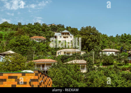 Dilijan,Armenia,August 24,2018:View of the suburb of Dilijan with low houses, among the gardens  located on a hill against the blue sky - Stock Photo