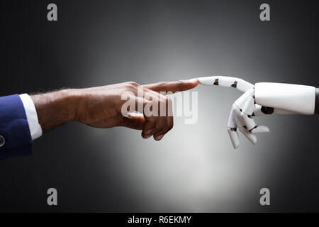 Fingers Of Robot And Man Touching - Stock Photo