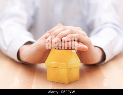 Small yellow house protected by hands - Stock Photo