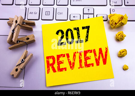 Hand writing text caption inspiration showing 2017 Review. Business concept for Annual Summary Report written on sticky note paper on the white keyboard background. - Stock Photo