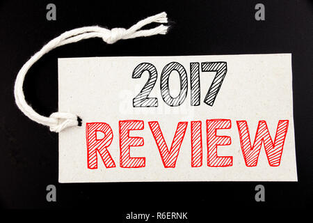 Handwritten text caption showing 2017 Review. Business concept writing for Annual Summary Report written on price tag paper on the black vintage background. - Stock Photo