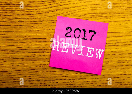 Handwriting Announcement text showing 2017 Review. Business concept for Annual Summary Report written on sticky note empty paper, wooden background with copy space, sunglasses. - Stock Photo