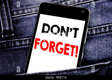 Writing text showing Do Not Forget. Business concept for Reminder Message written mobile cell phone with copy space in the back pants trousers pocket - Stock Photo