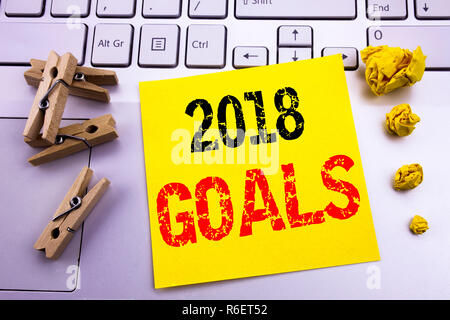 Hand writing text caption inspiration showing 2018 Goals. Business concept for financial planning, business strategy written on sticky note paper on the white keyboard background. - Stock Photo