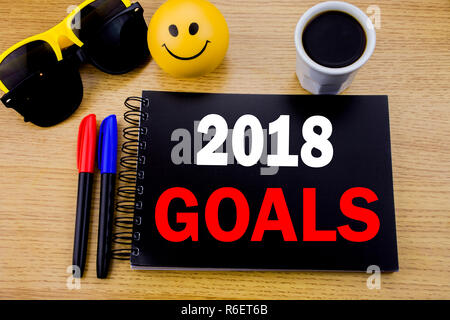 Conceptual hand writing text caption showing 2018 Goals. Business concept for financial planning, business strategy written on sticky note with space on old wood wooden background with sunglasses - Stock Photo