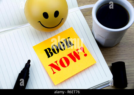 Writing text showing Book Now. Business concept for Reservation Booking written sticky note empty paper, Wooden background with copy space, Coffee and marker - Stock Photo