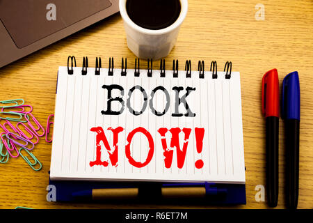 Hand writing text caption showing Book Now. Business concept for Reservation Booking written on notebook book on the wooden background in the Office with laptop coffee - Stock Photo