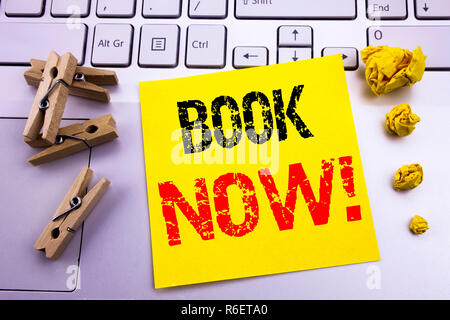 Hand writing text caption inspiration showing Book Now. Business concept for Reservation Booking written on sticky note paper on the white keyboard background. - Stock Photo