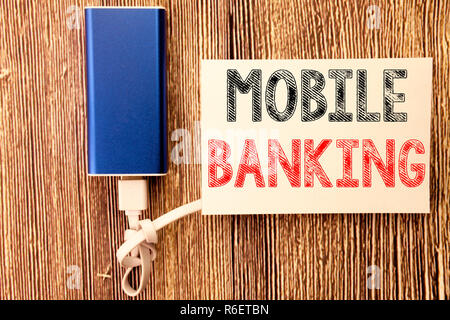 Conceptual hand writing text caption inspiration showing Mobile Banking. Business concept for Internet Banking e-bank written on sticky note old wood wooden background with power bank - Stock Photo
