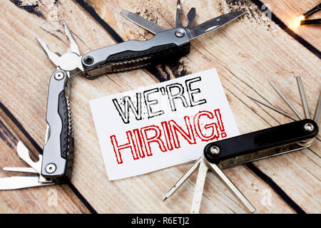 Conceptual hand writing text caption inspiration showing We Are Hiring Now. Business concept for Recruitment Human Resources  Written on sticky note wooden background with pocket knife - Stock Photo