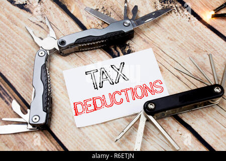 Conceptual hand writing text caption inspiration showing Tax Deductions. Business concept for Finance Incoming Tax Money Deduction Written on sticky note wooden background with pocket knife - Stock Photo