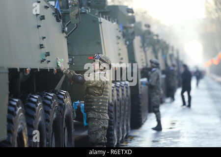 BUCHAREST, ROMANIA - December 1, 2018: Romanian soldiers are cleaning armoured vehicles before the Romanian National Day military parade - Stock Photo